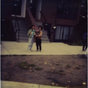Two girls standing on the sidewalk in front of Villa Victoria row houses.