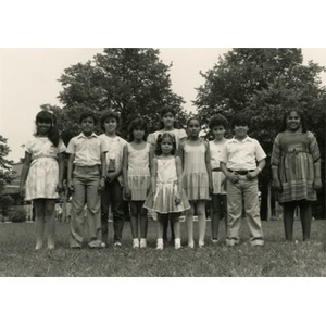 Group portrait of ten unidentified children standing in a park.