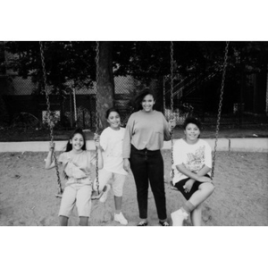 Four unidentified girls posing at the swing set in a playground.