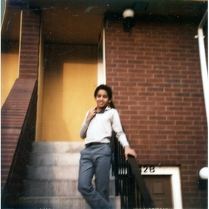 Boy standing on the front steps of a Villa Victoria row house.