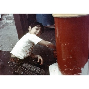 Little boy painting a column bright red.
