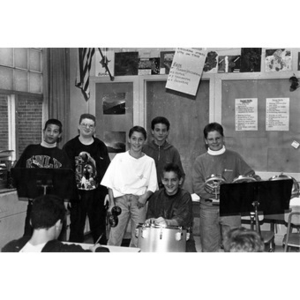 Boys in a Latin percussion class posing for a group photograph in a classroom.