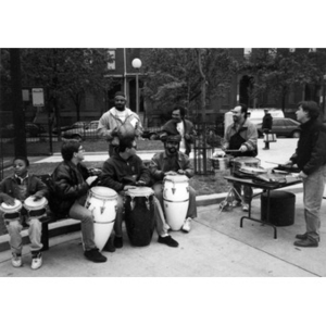 Latin Percussion group making music in a neighborhood park.