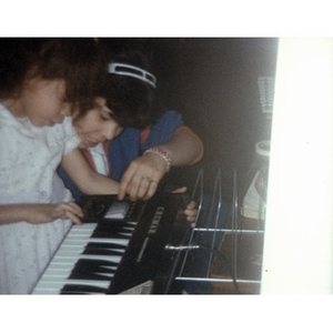 Two little girls playing a keyboard.