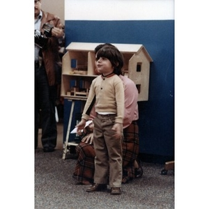 Boy standing in a room with a dollhouse.