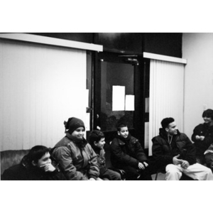 Boys sitting in an indoor space wearing coats and hats.