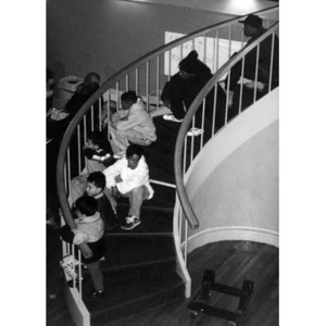 Teens and children sitting on the spiral staircase at the Jorge Hernandez Cultural Center.