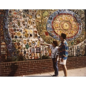 Couple with a baby pointing out details of the Plaza Betances mural.