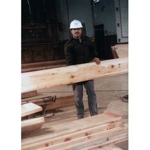 Construction worker holding a plank of wood during the renovation work that transformed the All Saints Lutheran Church into the Jorge Hernandez Cultural Center.