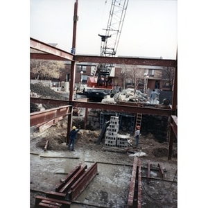 Crane, workmen, and steel beam framing on the Taino Tower construction site.