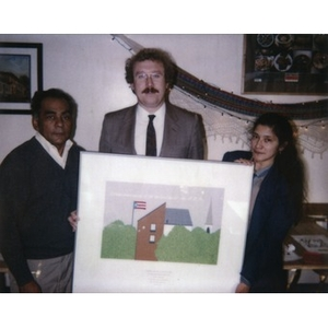 Clara Garcia and two unidentified men hold up a limited edition serigraph designed by Joaquin Reyes which depicts Villa Victoria.