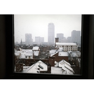View out a window of the rooftops of Villa Victoria in the snow with Boston's skyline in the distance.