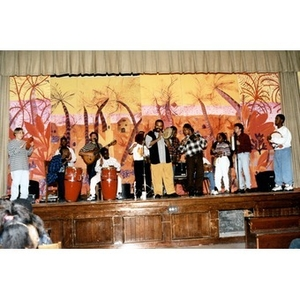 A band composed of Inquilinos Boricuas en Acción musicians and school children making music on a school stage.