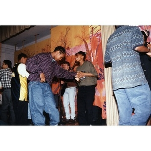 High school students dancing together on stage during a music and dance program organized by Inquilinos Boricuas en Acción's Areyto.