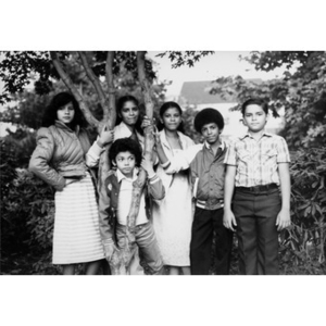 Group photograph of six children standing outside under a tree.