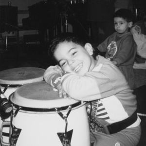 Little boy resting his head on a conga drum.