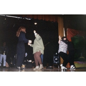 Women dancing on stage to music provided by the band behind them.