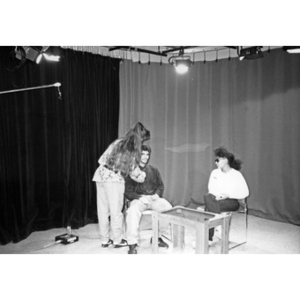 Young woman attaching a microphone to a young man on the set of Villa Victoria's public access television station.