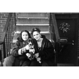 Two teenage girls and a dog sitting on front steps of a Villa Victoria row house.