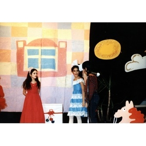 Children in an Areyto program performing in a play on stage.