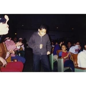 Boy walking down an aisle while the audience members in the auditorium applaud.