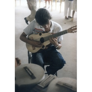 Young man playing a small guitar or cuatro.