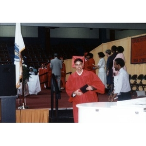 Young man in red cap and gown at a graduation ceremony.