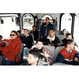 Villa Victoria children and chaperones seated on a bus or shuttle while on a field trip.
