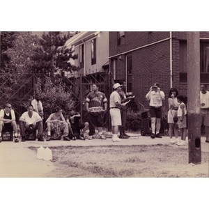 People standing and sitting around the edges of a grassy area behind Villa Victoria townhouses.