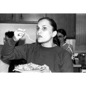 Young woman pauses with a fork halfway to her mouth during a community gathering.