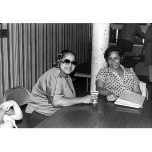 Two women sitting together at one end of a table during a community gathering.
