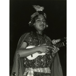 Young performer in traditional costume playing a ukulele-like instrument.