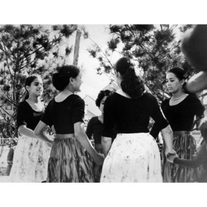 Young women dancing in a ring on an outdoor stage.
