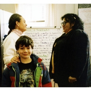 Boy smiling for the camera while two women stand behind him conversing.