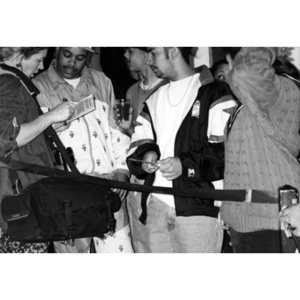 Young people gathered around a female reporter with a large camera bag slung over her shoulder.