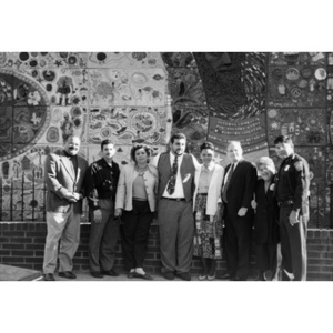 Eight men and women posing for a group photograph in front of the ceramic tile mural.