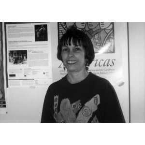 Portrait of a woman with short hair and long earrings standing in front of a poster.