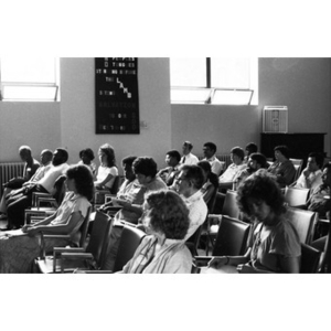 Unidentified people sitting in a large classroom or auditorium listening to speakers at the front of the room.