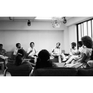 Group of people sitting around the edges of a room listening to an unidentified man and taking notes.