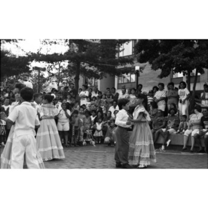 Children dance in pairs before a crowd of spectators at the Festival Betances.