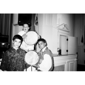 Three boys pose by the edge of the stage holding tambourines.