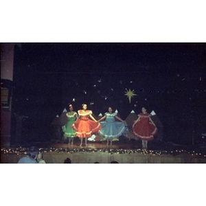 Young girls perform a folk dance on stage during a Three Kings Day celebration.