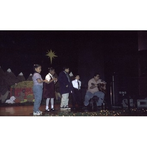 Man with guitar and four small children on stage during a celebration of Three Kings Day.
