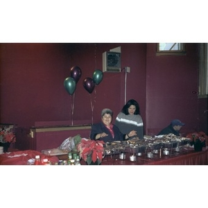Inquilinos Boricuas en Acción staffer Carmen Colombani and another woman preside over the food table at a Three Kings Day celebration.