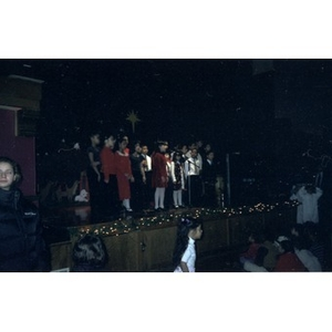 Children singing on stage at the Jorge Hernandez Cultural Center during a Three Kings Day celebration.