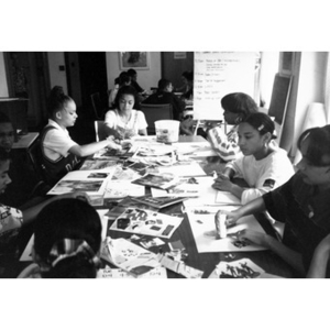 Young people making collages at a large table.