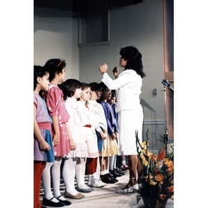 Woman conducting children's choir at the opening of the Villa Victoria Cultural Center.
