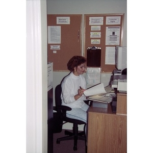 Woman sitting at her desk in her office, possibly at Residencia Betances.