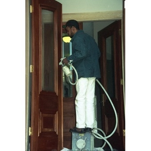 Workman Using An Airbrush To Paint The Front Doors Of Residencia Betances.