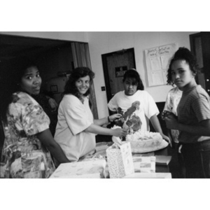 Women preparing to cut a cake during an office celebration.